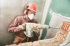 Worker with demolition hammer breaking interior wall Royalty Free Stock Photography