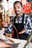 Worker demonstrating assortment in leather. Happy male worker demonstrating assortment in leather workshop Stock Photos