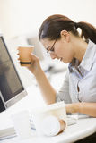Worker At Desk With Coffee. Female Office Worker At Computer Drinking Coffee at Messy Desk stock photos
