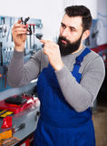Worker diagnose broken part of  scooter Royalty Free Stock Image