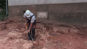 Worker dig out ground in trench. In summer day stock video footage