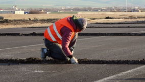 Worker dig trenches to lay cables for the airfield lighting system. TULCEA, ROMANIA - DECEMBER 02: Worker dig trenches to lay cables for the airfield lighting stock video footage