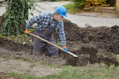 Construction worker digging trench using shovel. Worker digging trench at construction site for pipeline or for wall, real people working royalty free stock photography