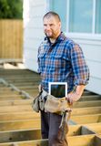Worker With Digital Tablet And Hammer In Tool Belt Royalty Free Stock Image
