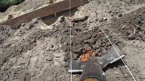 Worker digs a shovel trench at a construction site. Layout foundation with a tight rope for precise digging stock video footage