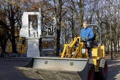 Worker on a dirt digging truck passing a statue in the streets of The Hague in The Netherlands stock image