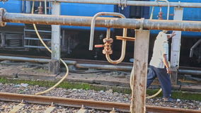 Worker Disconnects Water Pipes from Train System on Station. HAMPI, KARNATAKA/INDIA - MARCH 02 2012: Indian railway worker in shirt disconnects plastic water stock footage