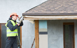 Worker dismantling roof shingles Stock Photo