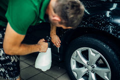 Worker disperses soapy water, paint protection. Worker disperses soapy water, preparing car for protect against chips and scratches. Paint protection. Protective Stock Photography
