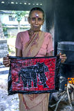 A worker displays a batik at the Baba Batik factory in Matale in Sri Lanka. A worker displays a batik after the wax has been melted off the garment at the Baba Stock Photos