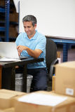 Worker In Distribution Warehouse Using Laptop Royalty Free Stock Photography