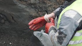 Worker in ditch with circular saw putting on red rubber gloves. Slowmotion stock video footage