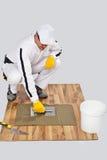 Worker DIY tile adhesive trowel wooden floor. Construction worker in white coveralls Applying Tile Adhesive with Notched Trowel on a wooden Floor bucket Stock Image