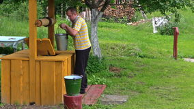 Worker draw full bucket water from wooden country well stock video