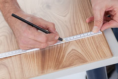 Worker drawing a mark on laminate Royalty Free Stock Photography