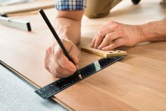 Worker drawing a mark on laminate Royalty Free Stock Images