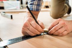 Worker drawing a mark on laminate using ruler Royalty Free Stock Photo