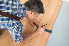 Worker drawing a mark on laminate using ruler Royalty Free Stock Photography