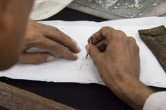 Worker drawing stencil motif on cloth Royalty Free Stock Photography