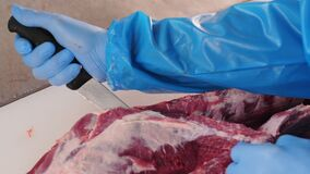 Worker dresses fresh meat with knife on table in workshop