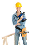 Worker With Drill And Tool Belt Standing By Work Horse. Portrait of confident female construction worker with drill and tool belt standing by work horse against Royalty Free Stock Photos