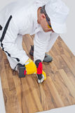 Worker drilled wooden floor cracks Royalty Free Stock Images