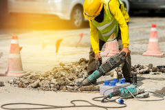 Worker drilling concrete driveway with jackhammer.Man repairing. Worker drilling concrete driveway with jackhammer Stock Photos