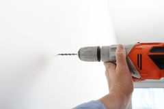 Worker drilling hole with electric power driller Stock Photos
