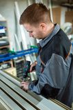 Worker with drilling mashine in workshop Stock Photography