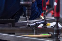 Worker drilling a part on a mounting table in the workshop.  Royalty Free Stock Image