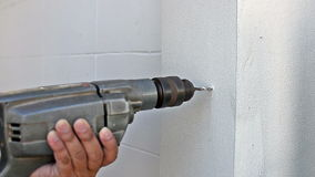 Worker drilling into wall Stock Image