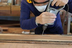 Worker drills a hole using electric drill machine in carpentry workshop. He is wearing safety equipment . royalty free stock photography