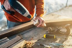 A worker drills a hole in wooden bar with drill stock image