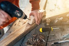 A worker drills a hole in wooden bar with drill stock photos