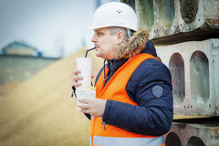 Worker drinking soda and eating french fries at construction site. In winter day Royalty Free Stock Image
