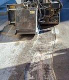 Worker driver Skid steer remove Worn Asphalt Stock Photo