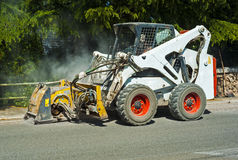 Worker driver Skid steer remove Worn Asphalt. During repairing Road Works Stock Photos