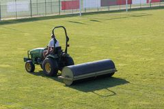 Worker Drives Lawn Equipment in Soccer Pitch before Match Stock Photography