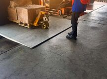 Worker driving forklift loading shipment carton boxes and goods on wooden pallet at loading dock from container truck to warehouse