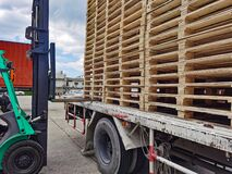 Worker driving forklift to loading and unloading wooden pallets from truck to warehouse cargo storage, shipment in logistics and