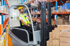 Worker is driving a pallet truck. In a warehouse Royalty Free Stock Image