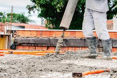 Worker dumping concrete over the slab. Of a house under construction. Structural parts of a house, building background. Steel beams and electrical mains piping royalty free stock images