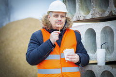 Worker eating french fries at construction site. In winter day Royalty Free Stock Photography