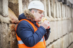 Worker eating hamburger at outdoor near wall. In winter day Royalty Free Stock Photo