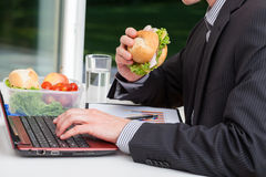 Worker eating at his desk royalty free stock photos