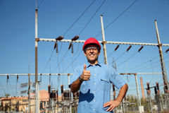 Worker at an Electrical Substation. Thumb up given by smiling engineer next to electrical substation. Selective focus Royalty Free Stock Photos