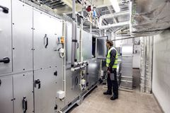 Worker in electrical switchgear room. Of CNC plant royalty free stock image
