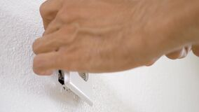 Worker electrician repair an electrical outlet in apartment