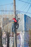 Worker electrician repairs wires on the street pole standing on the stairs Stock Image