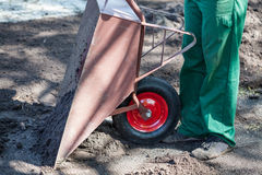 Worker empties a wheelbarrow Stock Photo